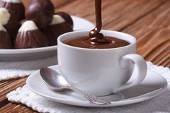 Chocolate is poured into a cup closeup on background sweets Royalty Free Stock Image