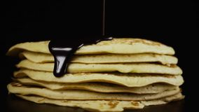 Chocolate is poured onto a pancake against a black background. Slow motion stock video footage