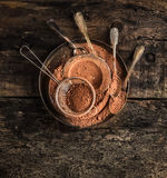 Chocolate powder in metall plate with spoons on dark wooden background. Top view Royalty Free Stock Photography