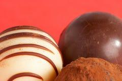 Chocolate Praline - Schokoladenpraline. Three chocolate pralines on red background - drei Schokopralinen vor rotem Hintergrund stock images