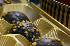 Chocolate Pralines. Close-up of chocolate pralines in festive gold box at Christmastime stock photo