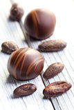 Chocolate pralines and cocoa beans Royalty Free Stock Photography