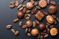 Chocolate pralines and cocoa beans Royalty Free Stock Photos