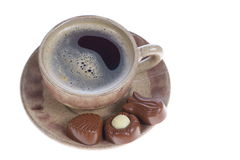 Chocolate pralines cup with black coffee on white Royalty Free Stock Images