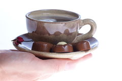 Chocolate pralines cup with black coffee on white Royalty Free Stock Photos