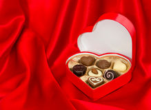 Chocolate pralines in golden box over red silk Royalty Free Stock Images