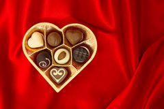 Chocolate pralines in golden heart shape box. Over red silk background Stock Photography