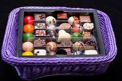 Chocolate pralines in lavender basket Stock Photos