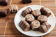 Chocolate pralines on old wooden table Stock Photos