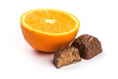Chocolate pralines with orange flavor near an orange Royalty Free Stock Photography