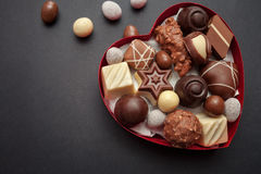 Chocolate pralines in red heart shape box. On black background stock photos