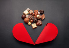 Chocolate pralines and red heart shaped box with for Valentines Stock Images