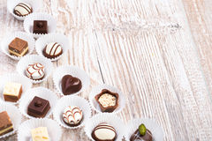 Chocolate pralines on wood, text space Stock Images
