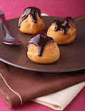 Chocolate profiteroles Stock Photos