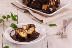 Chocolate profiteroles. Chocolate profiteroles with whipped cream on white dish royalty free stock images