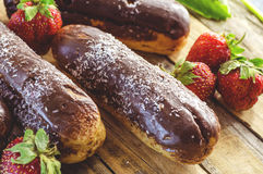 Chocolate profiteroles and strawberries. Chocolate profiteroles and fresh strawberries on a wooden table Royalty Free Stock Photography