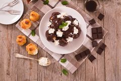 Chocolate profiteroles. Chocolate profiteroles with whipped cream on white dish stock photos