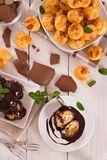Chocolate profiteroles. Chocolate profiteroles with whipped cream on white dish stock photography