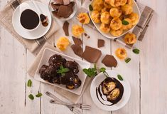 Chocolate profiteroles. Chocolate profiteroles with whipped cream on white dish royalty free stock photo