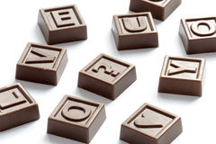 Chocolate puzzle. Scattered letters and signs made of chocolate Stock Photos