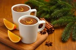Chocolate quente com laranja e especiarias na tabela de madeira rústica imagens de stock