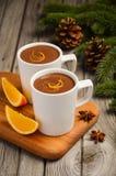 Chocolate quente com laranja e especiarias na tabela de madeira rústica imagem de stock