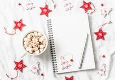 Chocolate quente com marshmallows e canela, bloco de notas vazio limpo, decorações do Natal em um fundo claro Inspirat do Natal imagens de stock