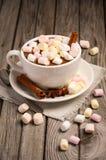 Chocolate quente com marshmallows e especiarias na tabela de madeira rústica imagens de stock royalty free
