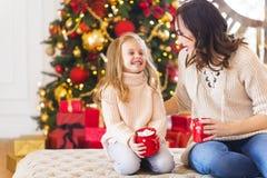 Chocolate quente com os marshmallows nas mãos da mulher e dela felizes Imagens de Stock