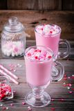 Chocolate quente cor-de-rosa com corações do marshmallow e do açúcar em uma caneca de vidro para Valentine Day Fotografia de Stock