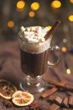 Chocolate quente em uma caneca transparente com as varas do chantiliy e de canela, as especiarias, as porcas e o pó de cacau em u fotografia de stock royalty free