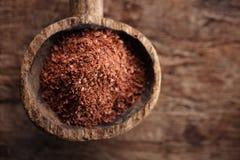 Chocolate rallado multa en cuchara de madera vieja Foto de archivo