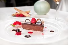 Chocolate and raspberries palette, served in a white plate. Chocolate and raspberries palette - tart rate with Ghana dehydrated raspberries and sherry Mariner royalty free stock image