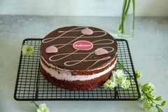 Chocolate and raspberry cake on a black baking tray with white flowers. Lying on a grey table royalty free stock images
