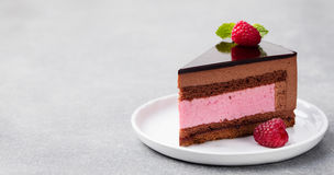 Chocolate and raspberry cake, mousse dessert on a white plate. Copy space.  stock photos