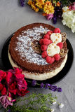Chocolate raspberry cream cake with flowers on a grey background.  Royalty Free Stock Photos