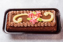 Chocolate rectangular cake decorated with cream roses on a light table. Sweet food is a confectionery business. copy space.  royalty free stock images