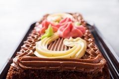 Chocolate rectangular cake decorated with cream roses on a light table. Sweet food is a confectionery business. copy space. Selective focus stock photos
