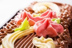 Chocolate rectangular cake decorated with cream roses on a light table. Sweet food is a confectionery business. copy space. Selective focus stock images