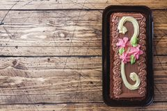 Chocolate rectangular cake decorated with cream roses on a wooden background. Sweet food is a confectionery business. Top view. Copy space royalty free stock photography