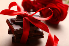 Chocolate with red ribbon and roses Stock Images