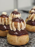 French chocolate cream puffs (religieuse). French chocolate religieuse (cream puffs assembled to look like nuns), chocolate filling and glaze, vanilla icing Royalty Free Stock Images