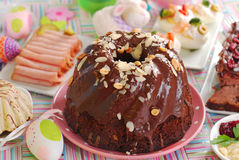 Chocolate ring cake with almonds and nuts for easter. Chocolate ring cake with almonds and nuts topping on easter table Royalty Free Stock Photos