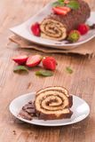 Chocolate roll with hazelnuts and strawberries. Stock Photos