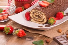 Chocolate roll with hazelnuts and strawberries. Royalty Free Stock Image