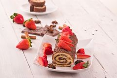 Chocolate roll with hazelnuts and strawberries. Royalty Free Stock Photography