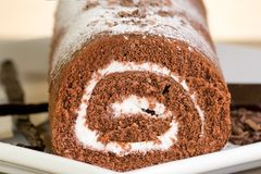 Chocolate roll with vanilla cream. Delicious chocolate and vanilla cake roll Stock Image