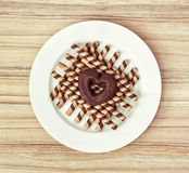 Chocolate rolls and heart shaped gingerbread cookie, symbol of l Stock Photography