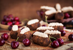 Chocolate rum balls cakes decorated with cream and fresh cherry Royalty Free Stock Image