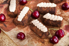 Chocolate rum balls cakes decorated with cream and fresh cherry royalty free stock photo